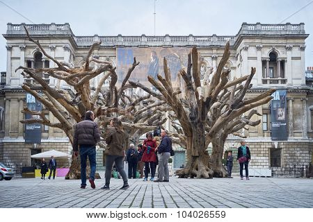 LONDON, UK - SEPTEMBER 23: Visitors appreciating Ai Wei Wei's installation 'Tree' in the forecourt of the Royal Academy of Arts. September 23, 2015 in London.