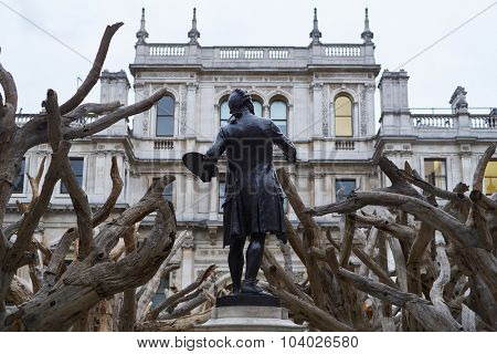 LONDON, UK - SEPTEMBER 23: Statue of Sir Joshua Reynolds amongst Ai Wei Wei's installation 'Tree' in the forecourt of the Royal Academy of Arts. September 23, 2015 in London.
