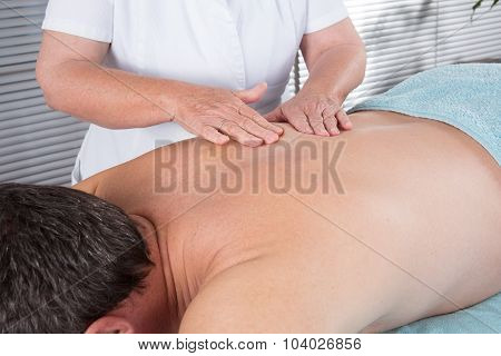 Cheerful Young Man Getting Back Massage At Spa