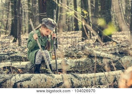 little girl in the woods sitting on a stump. vintage style
