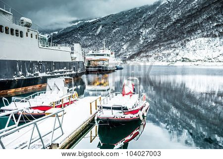 The ships and boats on the mooring in the Norwegian fjords in the winter