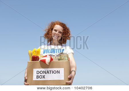 Volunteer Carrying Food Donation Box