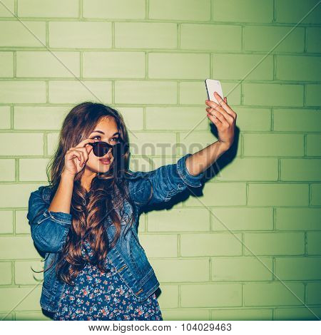Beautiful Long-haired Woman With A Smartphone Near A Green Brick Wall