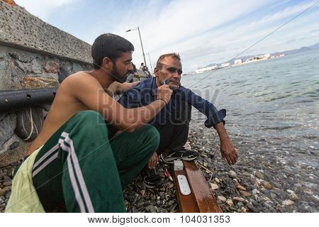 KOS, GREECE - SEP 27, 2015: Refugee shaves the other on the beach. Kos island is located just 4 kilometers from Turkish coast, and many refugees come from Turkey in an inflatable boats.