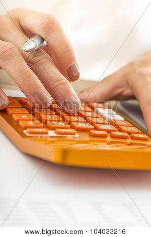 Closeup Of Female Student Hand Calculating Using Orange Desk Calculator