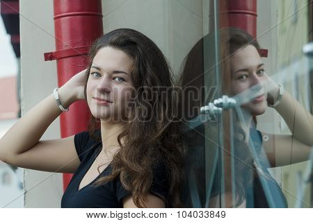 Glass Portrait Of Daydreaming Attractive Brunette Girl Posing Near Glass Display Window With Symmetr