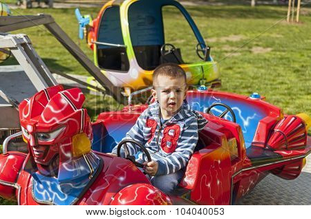 Boy Driving Car Toy In The Amusement Park