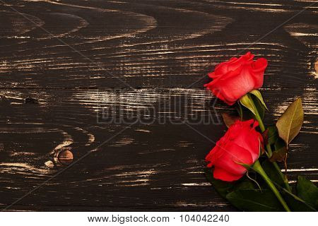 close-up photo of two red roses on grunge wooden background