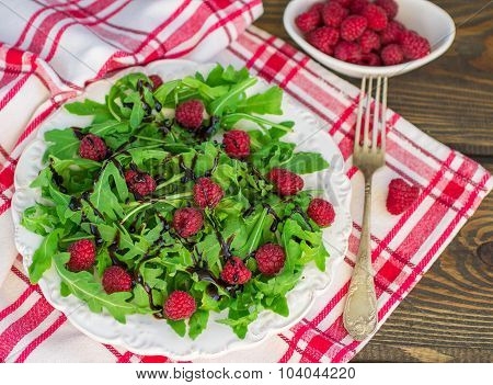 Delicious arugula salad with raspberries and balsamic vinegar in a white plate. Selective focus