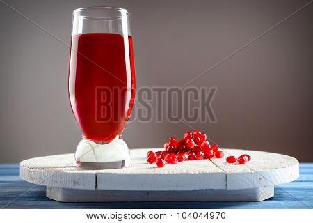 Fresh garnet juice with fruit on gray background