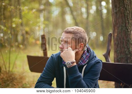 man thinking sitting at autumn park, selective focus