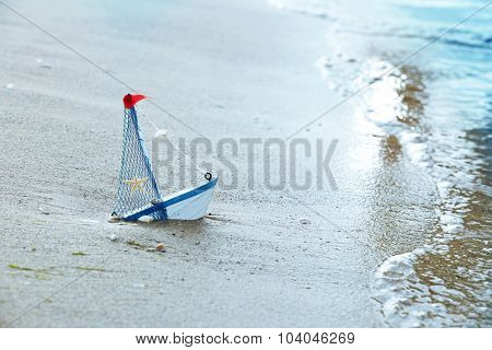 Small ship on sand beach background
