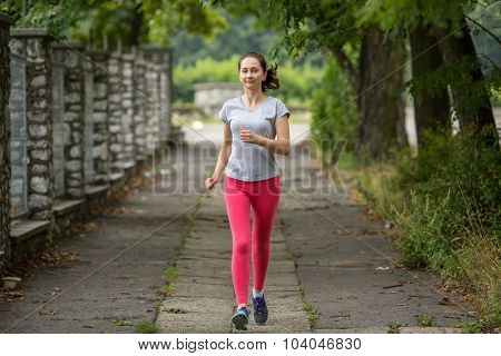 Young sports girl during a jog in the Park. Running, healthy lifestyle.