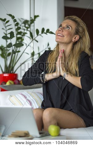 Young blond business woman sitting in front of a laptop folded in gratitude to hands.