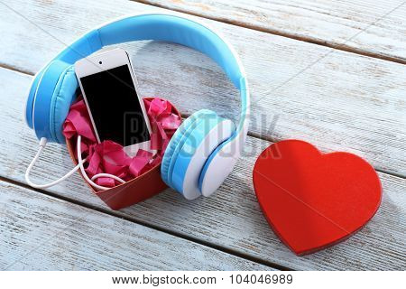 blue headphones with heart and phone on wooden background