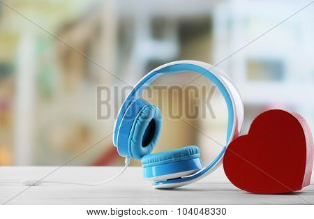 blue headphones with heart on defocused background