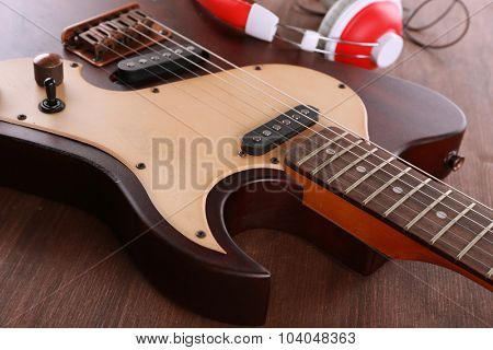 Electric guitar with headphones on wooden table close up