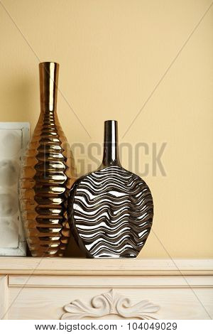 Modern vases with decor on fireplace in room