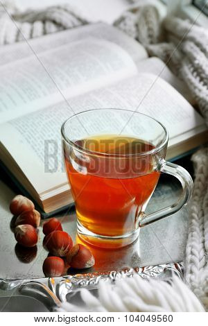 Cup of tea with book on metal tray, closeup