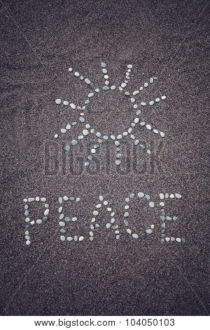 Peace Word And Sun Symbol On The Sand - Toned Photo.