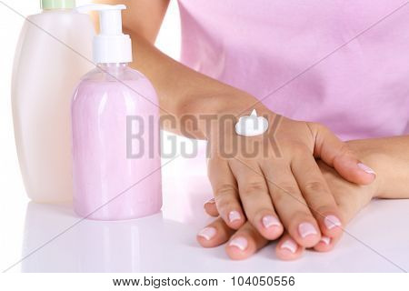 Women applying cream on her hands closeup