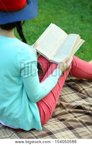 Young woman with book sitting on green grass outdoors