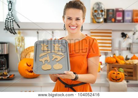 Happy Housewife Holding Tray Of Uncooked Halloween Biscuits