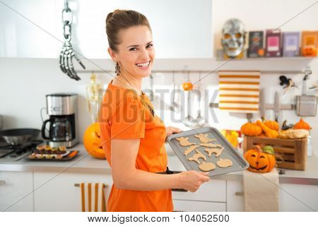 Happy Woman Holding Tray Of Uncooked Halloween Biscuits