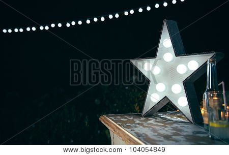 White star lamp with light bulbs over wooden table