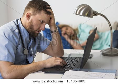 Overworked Doctor Sitting At Computer