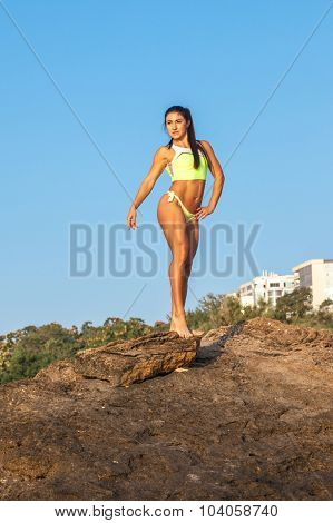 Women Athlete on a rock by the sea against the sky
