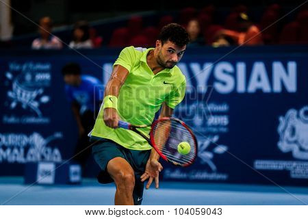 KUALA LUMPUR, MALAYSIA - OCTOBER 01, 2015:Grigor Dimitrov of Bulgaria hits a backhand return in his match at the Malaysian Open 2015 Tennis tournament held at the Putra Stadium, Malaysia.