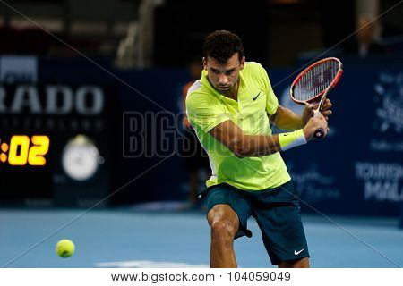 KUALA LUMPUR, MALAYSIA - OCTOBER 01, 2015:Grigor Dimitrov of Bulgaria attempts a backhand return in his match at the Malaysian Open 2015 Tennis tournament held at the Putra Stadium, Malaysia.