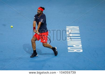 KUALA LUMPUR, MALAYSIA - OCTOBER 01, 2015: Marcos Baghdatis of Cyprus plays a backhand return during his match at the Malaysian Open 2015 Tennis tournament held at the Putra Stadium, Malaysia.
