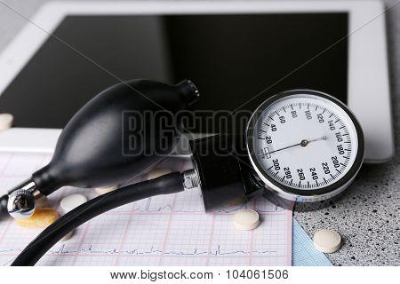 Blood pressure meter, stethoscope, digital tablet on gray background