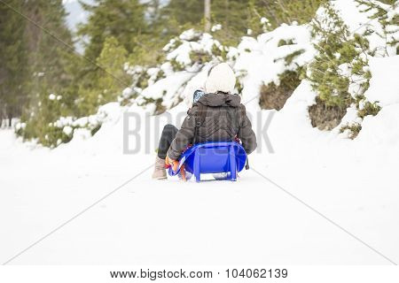 View From Behind Of A Mother Sitiing In A Toboggan With Her Child