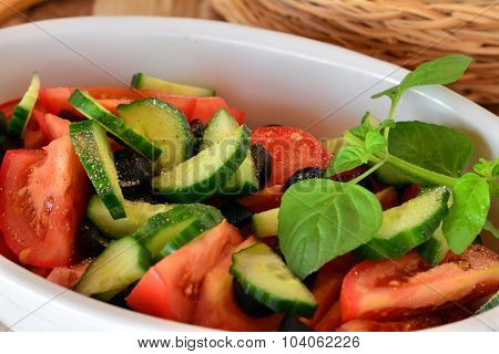 Fresh mixed vegetable salad with cucumber and tomatoes with balsamic