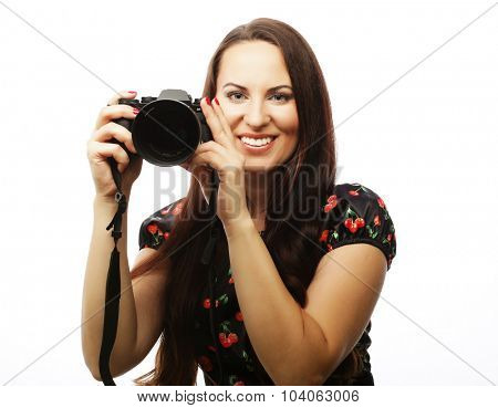 Cheerful young woman making photo on camera over white background