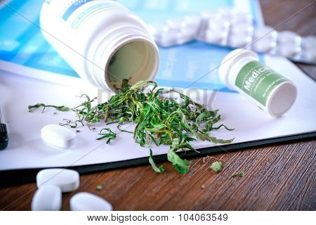 Bottle of dry medical cannabis and pills with clipboard on table close up