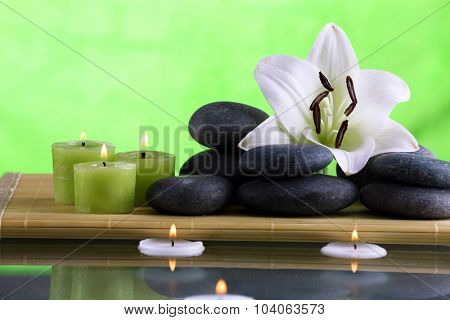 Still life with spa stones on green background