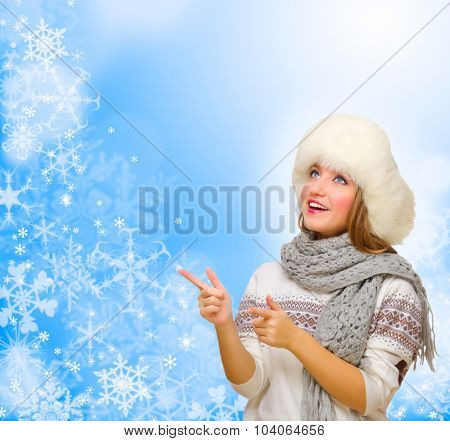 Young girl shows pointing gesture on winter background