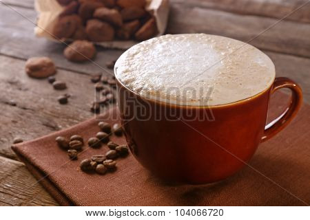 Cup of coffee on napkin, coffee beans and biscuits in paper bag on wooden background
