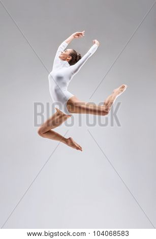 Young slim gymnast in studio
