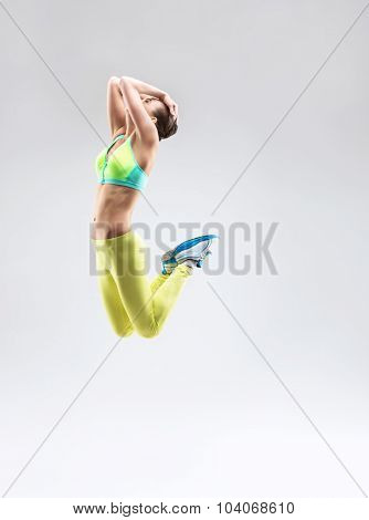 Jumping girl in sportswear in the studio