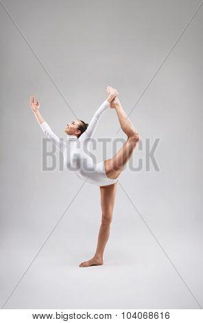Young slim gymnast in studio