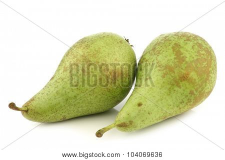 two fresh conference pears on a white background