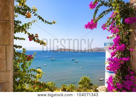 Clear Blue Waters And Beautiful Flowers Can Be Seen Past The Lighthouse At Ortakent In Turkey