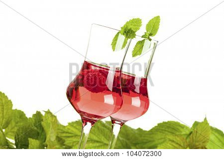 two glasses of raspberry liqueur decorated with peppermint in front of raspberry leaves, tilted view, isolated on white background