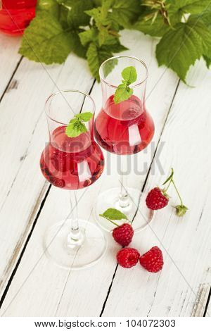 two glasses of raspberry liqueur, stray berries, leaves in background, on rustic white table