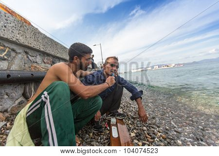 KOS, GREECE - SEP 27, 2015: Refugees shaves on the beach. Kos island is located just 4 kilometers from Turkish coast, and many refugees come from Turkey in an inflatable boats.